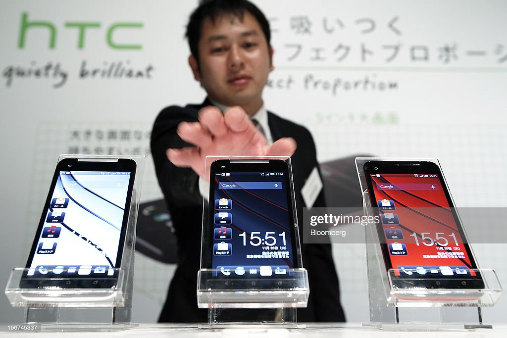 An employee adjusts a row of HTC J Butterfly smartphones, produced by HTC.Corp. during the unveiling event in Tokyo, Japan, on Tuesday, Nov. 20, 2012. Taiwan's HTC Corp. needs to improve its global brand awareness to gain share in China, and its newly unveiled model is likely to help the vendor do that. Photographer: Kiyoshi Ota/Bloomberg via Getty Images