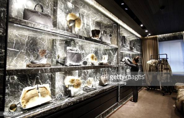 An employee adjusts an illuminated display of footwear and bags inside a Moncler luxury skiwear store operated by Moncler SpA in Milan Italy on...