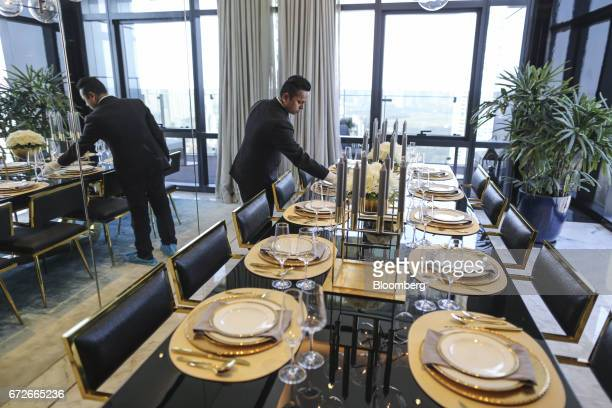 An employee adjusts dinnerware on a table inside a show home at Lodha Altamount a luxury residential project developed by Lodha Developers Ltd in...