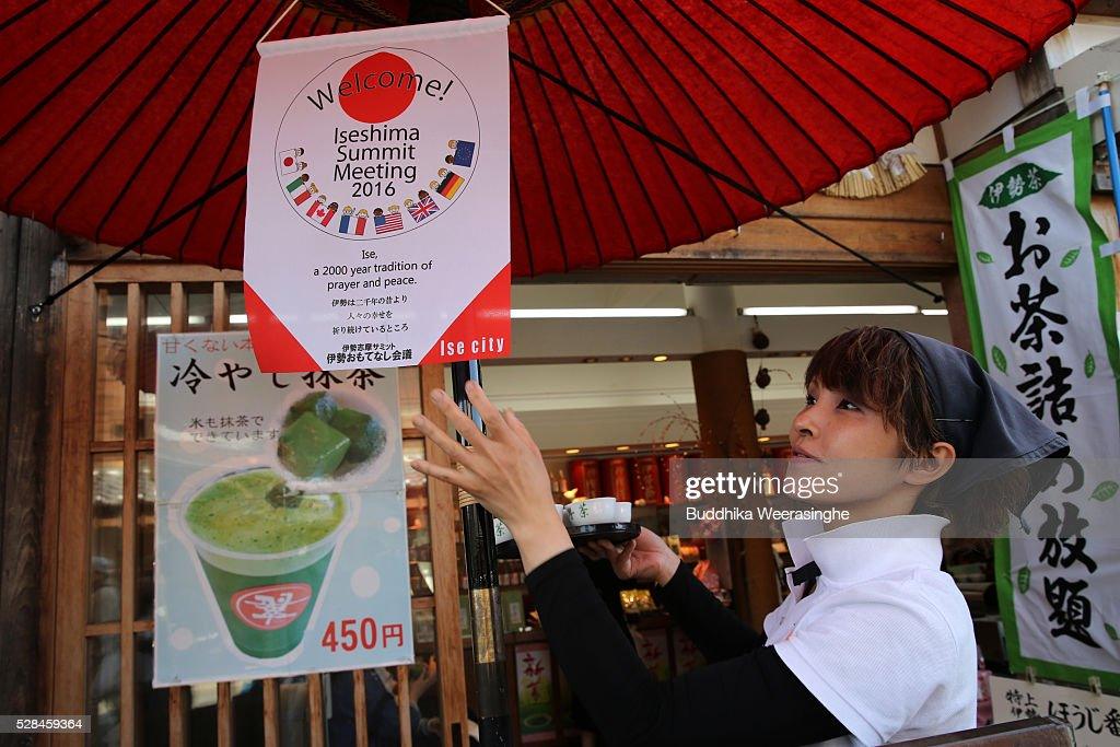 An employee adjusts the G7 Ise-Shima summit welcome flag below the traditional Japanese tea ceremony umbrella in front of the SUI Tea Shop at Okage Yokocho, a traditional shopping street on May 5, 2016 in Ise, Japan. Ise-Shima prepares for the G7 summit which is to be held on May 26 and 27, 2016.