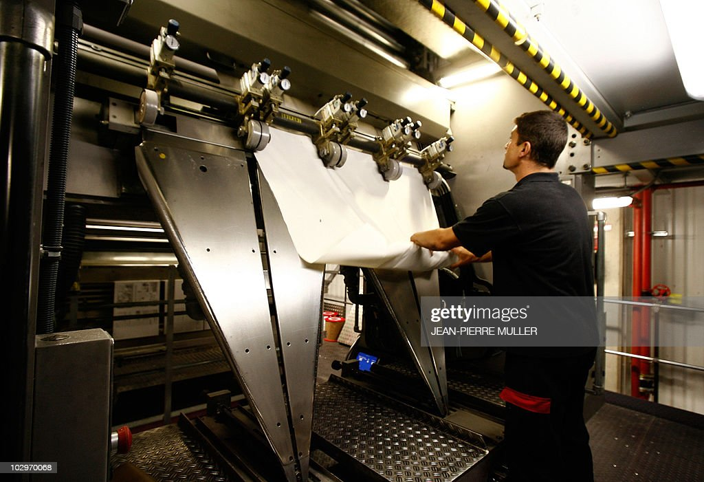 An employee adjusts the paper roll on a rotary printing press machine in the basement of the newspaper on February 19, 2008 in Bordeaux, southern France.