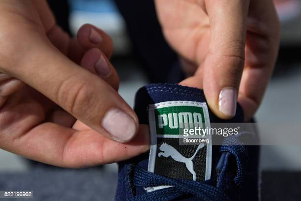 An employee adjusts the tongue of a trainer inside a Puma SE sportswear clothing store in Berlin Germany on Tuesday July 25 2017 Puma increased its...