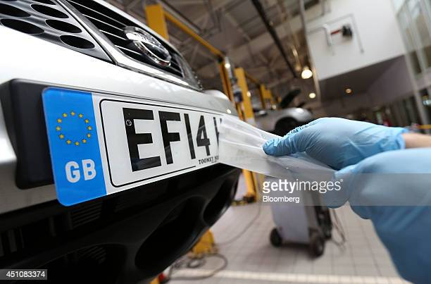 An employee affixes a number plate to the front fender of a new Nissan Juke automobile produced by Nissan Motor Co during a predelivery check for a...