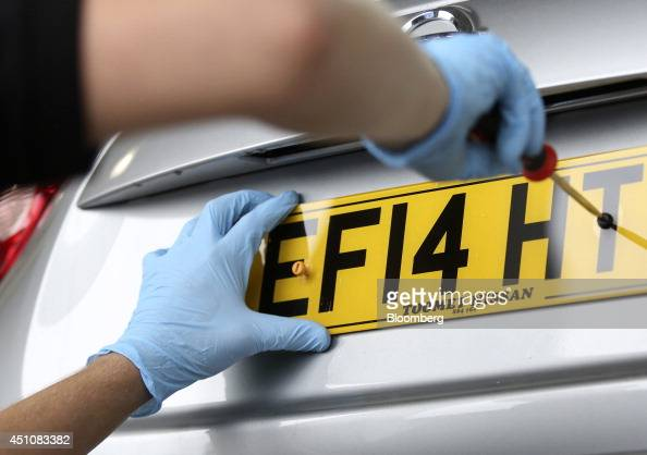 An employee affixes a number plate to the trunk of a new Nissan Juke automobile produced by Nissan Motor Co during a predelivery check for a customer...
