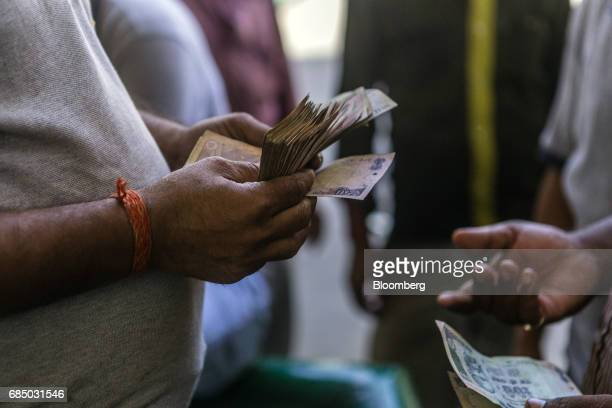 An employee and a customer handle Indian Rupee banknotes at an Indraprastha Gas Ltd gas station in New Delhi India on Wednesday May 17 2017...