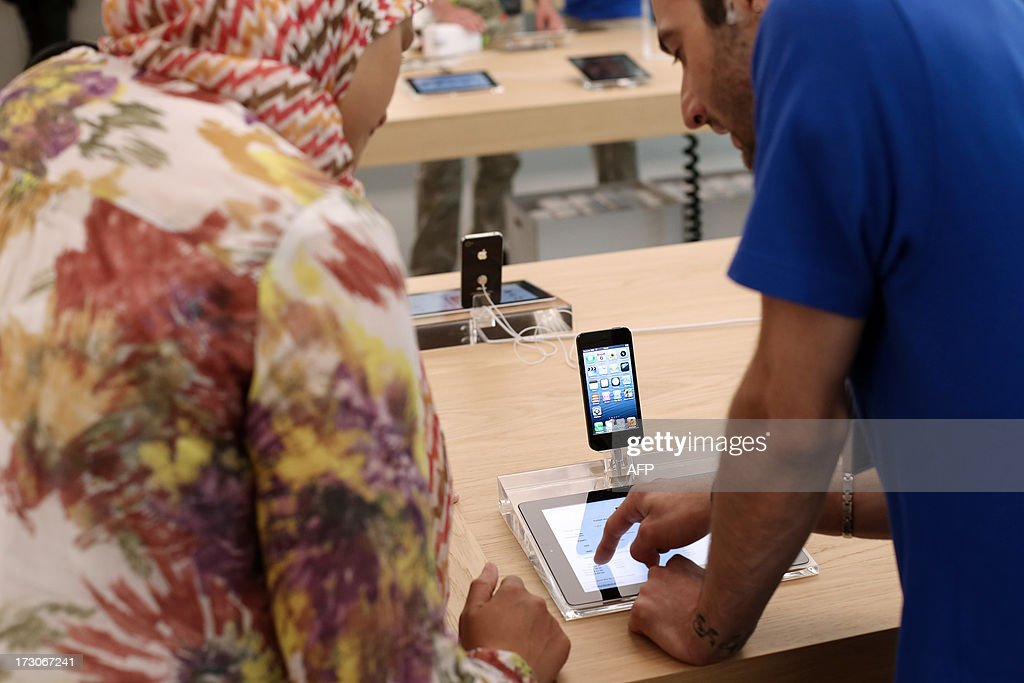 An employee and a customer look at Apple's iPhone 5 smartphones and iPads in a new Apple store on July 6, 2013 in Rosny-sous-Bois, near Paris.