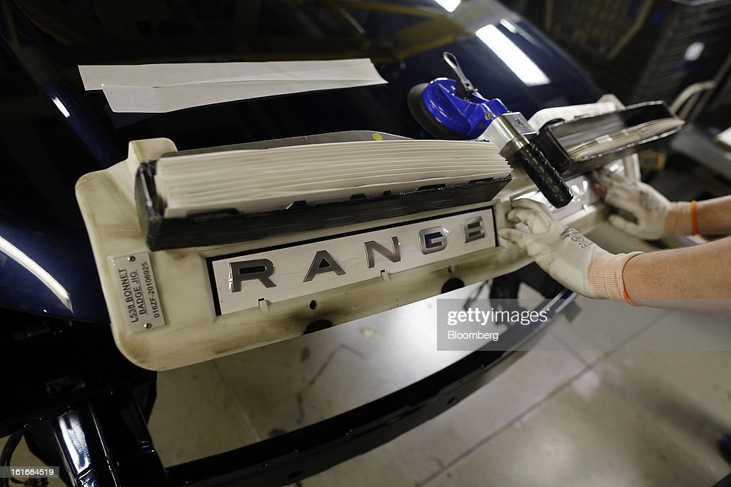An employee applies a logo to the hood of a Range Rover Evoque SUV automobile, produced by Jaguar Land Rover Plc, a unit of Tata Motors Ltd., as it travels along the production line at the company's assembly plant in Halewood, U.K., on Wednesday, Feb. 13, 2013. Carmakers from Ford Motor Co. to Audi AG and Jaguar Land Rover Plc are using record amounts of aluminium to replace heavier steel, providing relief to producers of the metal confronting excess supplies and depressed prices. Photographer: Simon Dawson/Bloomberg via Getty Images