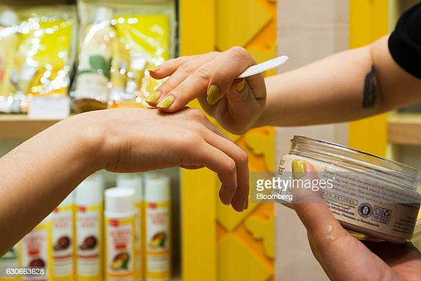 An employee applies a sample of moisturizer on a customer's hand at a Burt's Bees Inc store a subsidiary of Clorax Co in Seoul South Korea on...