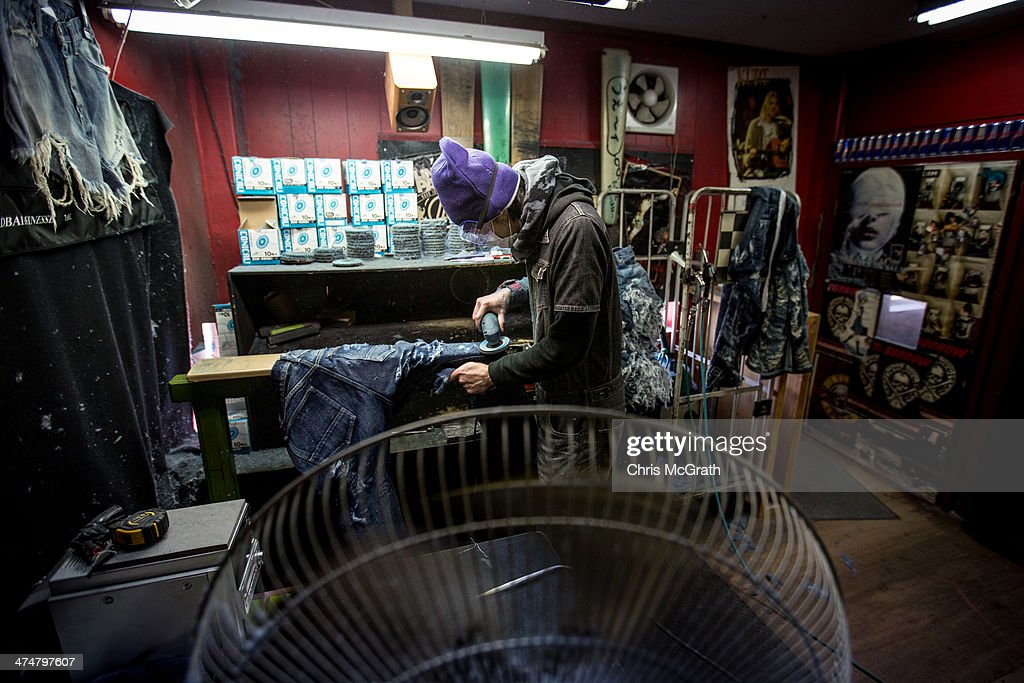 An employee applies damage marks to a pair of jeans at the Bitou denim processing facility in Kojima district on February 25 2014 in Kurashiki Japan...