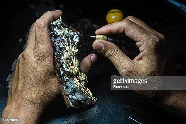 An employee applies diamond studs to a gold ornament piece at the Viswa Devji Diamonds Pvt factory in Coimbatore Tamil Nadu India on Thursday Nov 28...