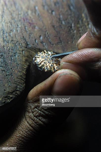 An employee applies diamond studs to a gold ornament piece at the Viswa Devji Diamonds Pvt factory in Coimbatore Tamil Nadu India on Thursday Nov 28...