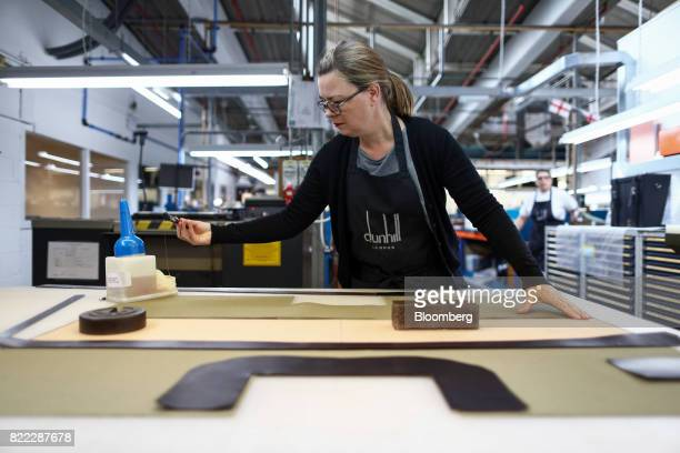 An employee applies glue to a section of canvas on a Kempton canvas tote bag at the Alfred Dunhill Ltd London Leather Workshop in London UK on...