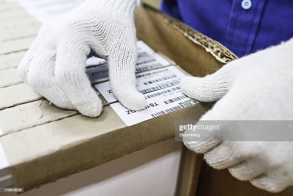 An employee applies labels to solar panel packaging at the Tata Power Solar Systems Ltd. manufacturing plant in Bangalore, India, on Tuesday, June 11, 2013. Tata Groups solar unit is expanding its business building plants for customers, forecasting that offices and factories will be paying more for grid power than solar by 2016 in most Indian states. Photographer: Dhiraj Singh/Bloomberg via Getty Images