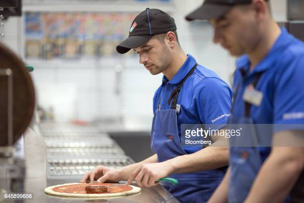 An employee applies tomato sauce to a pizza base inside a Domino's Pizza Group Plc store in Hanwell London UK on Monday Feb 27 2017 Domino's Pizza...