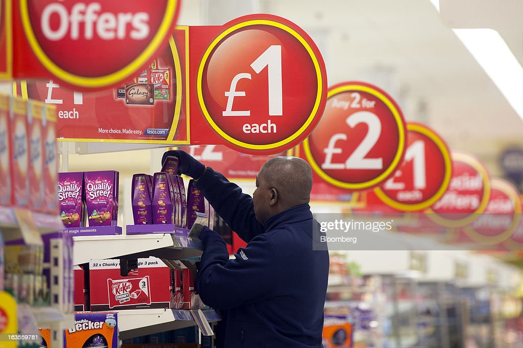 An employee aranges a display of Nestle SA Quality Street chocolates inside a Tesco Plc supermarket in the borough of Kensington in London, U.K., on Tuesday, March 12, 2013. Tesco Plc, the U.K.'s largest grocer launched a 'Price Promise', its latest initiative offering to match the price of customers' purchases to that of it's rivals, including Wal-Mart Stores Inc.'s ASDA. Photographer: Simon Dawson/Bloomberg via Getty Images