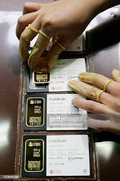 An employee arranges a 100g gold bar together with a 9999 fineness certificate from the Swiss bank UBS on April 6 2009 at a plant of gold refiner and...