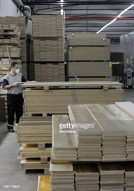 An employee arranges a block of wood laminate flooring after manufacture at the Tarkett Group factory in Backa Palanka Serbia on Tuesday Dec 13 2011...