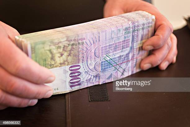 An employee arranges a bundle of 1000 Swiss Franc banknotes in the office of a bank in this arranged photograph in Zurich Switzerland on Friday Nov...