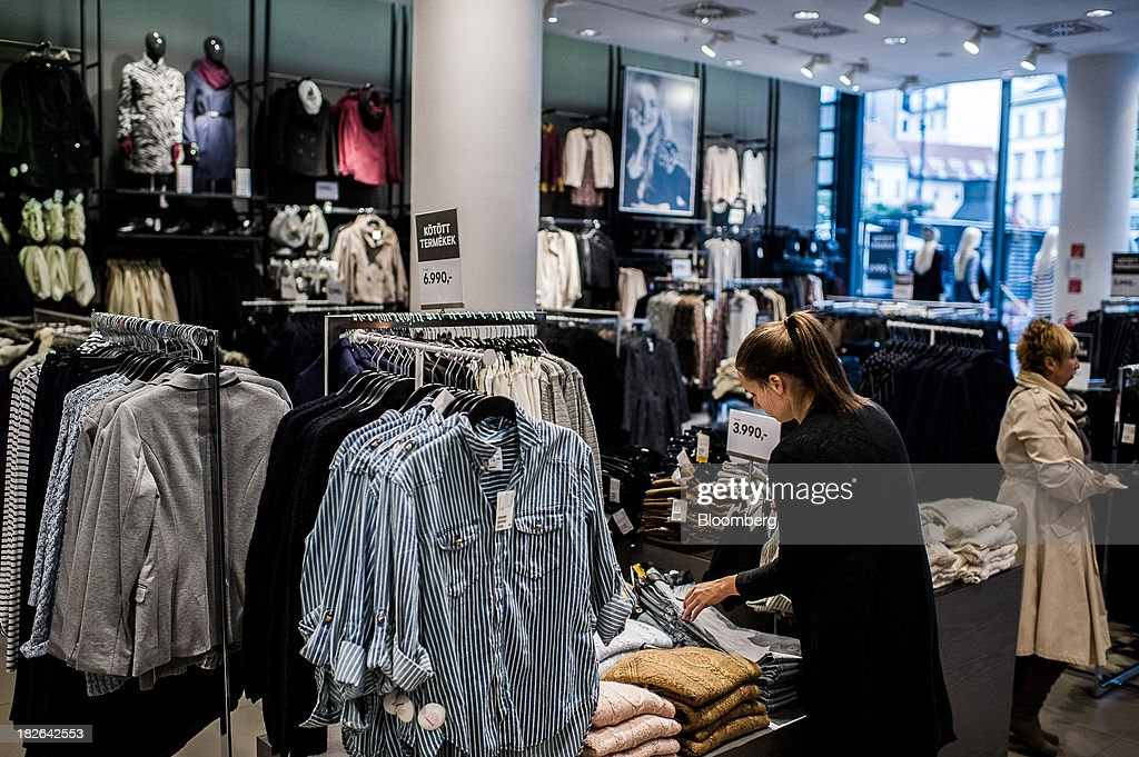 An employee arranges a clothes display inside a Hennes & Mauritz AB (H&M) fashion store in Budapest, Hungary, on Wednesday, Oct. 2, 2013. 'The retail sales environment in Europe, especially in Spain, has become less challenging in the last few weeks, while the weather overall has also been more stable,' Anne Critchlow, a London-based analyst at Societe Generale, said. Photographer: Akos Stiller/Bloomberg via Getty Images
