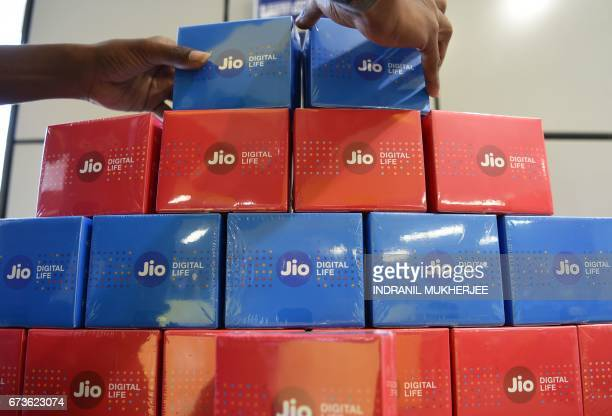 An employee arranges a display for JioFi devices at a Reliance Digital store in Mumbai on April 21 2017 Indian conglomerate Reliance Industries...