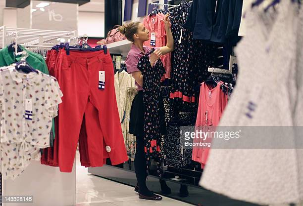An employee arranges a display in a Debenhams Plc store at Westfield London shopping mall operated by Westfield Group in London UK on Tuesday April...
