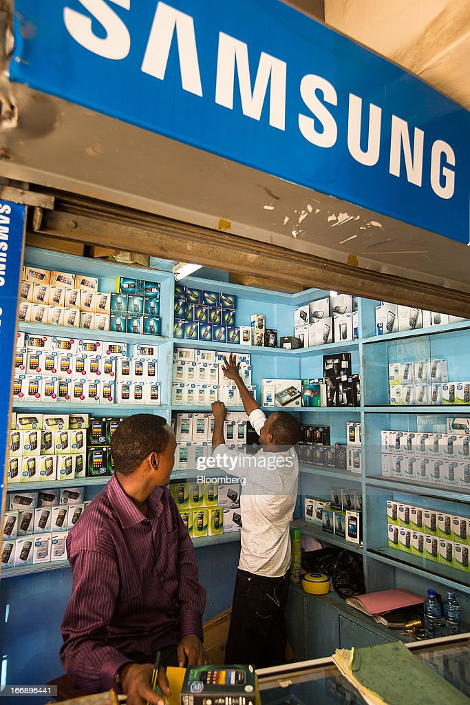 An employee arranges a display of boxes containing new mobile phones inside a store specialising in the sale of Samsung Electronics Co. handsets in Nairobi, Kenya, on Wednesday, April 17, 2013. Though only 23 percent of houses there have electricity and just 9 percent of roads are paved, mobile-phone penetration is 75 percent in the country, up from 5 percent in 2003. Photographer: Trevor Snapp/Bloomberg via Getty Images