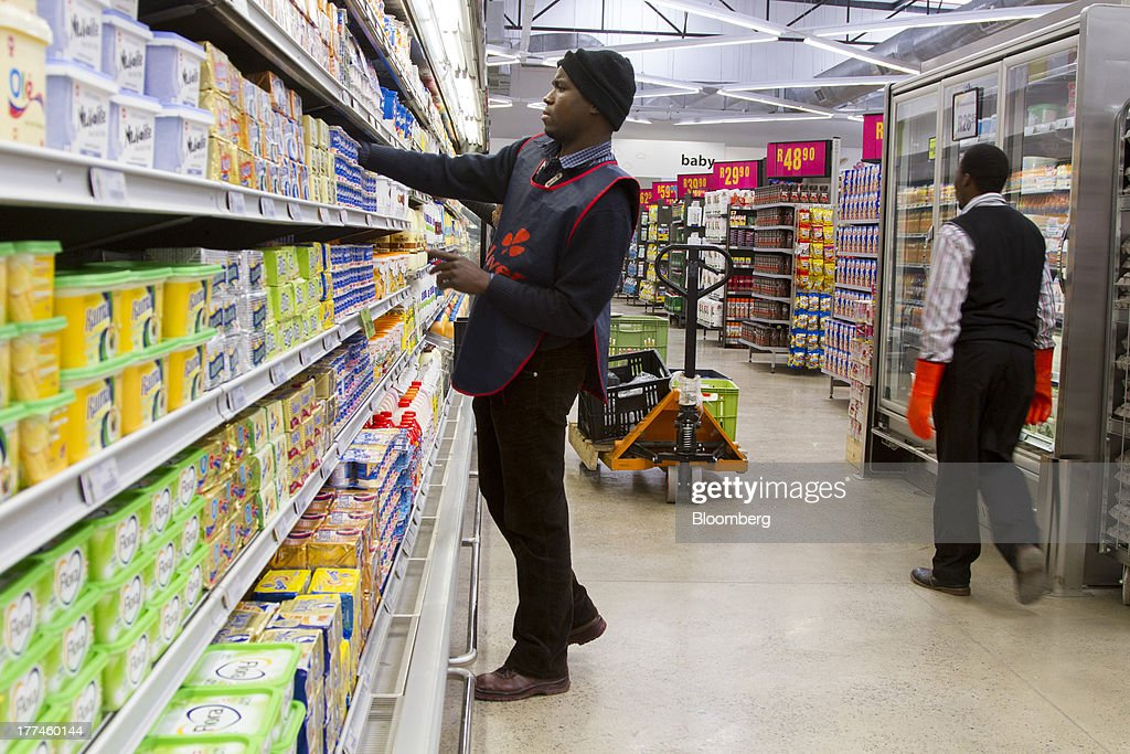 An employee arranges a display of dairy products in a refrigerated cabinet inside a Game supermarket, part of Massmart Holdings Ltd., in the Fourways district of Johannesburg, South Africa, on Thursday, Aug. 22, 2013. Massmart Holdings Ltd., the South African food and goods wholesaler owned by Wal-Mart Stores Inc., said revenue growth continued to slow in August after a downturn in consumer spending hurt first-half earnings. Photographer: Nadine Hutton/Bloomberg via Getty Images