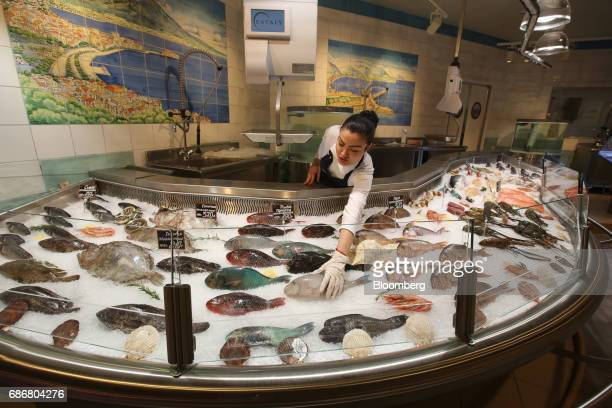 An employee arranges a display of fresh fish on ice inside the new Eataly food store operated by Eataly Net Srl at the Kievsky shopping mall in...