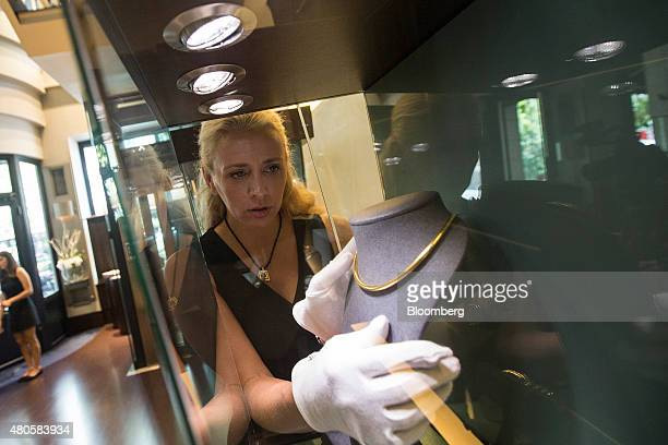 An employee arranges a display of jewelry in a window display at the Zolotos SA luxury jewelry store in Athens Greece on Monday July 13 2015 Greece...