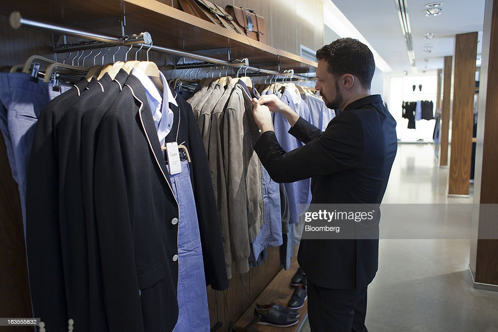 An employee arranges a display of men's clothing inside a Zara fashion store, operated by Inditex SA, in Madrid, Spain, on Tuesday, March 12, 2013. Europe's richest man, Amancio Ortega, the 76-year-old founder of Inditex SA, the world's biggest clothing retailer and owner of the Zara clothing chain, is No. 3 on Standard & Poor's 500 Index with a net worth of $57.4 billion, $4.9 billion ahead of Warren Buffett, 82. Photographer: Angel Navarrete/Bloomberg via Getty Images