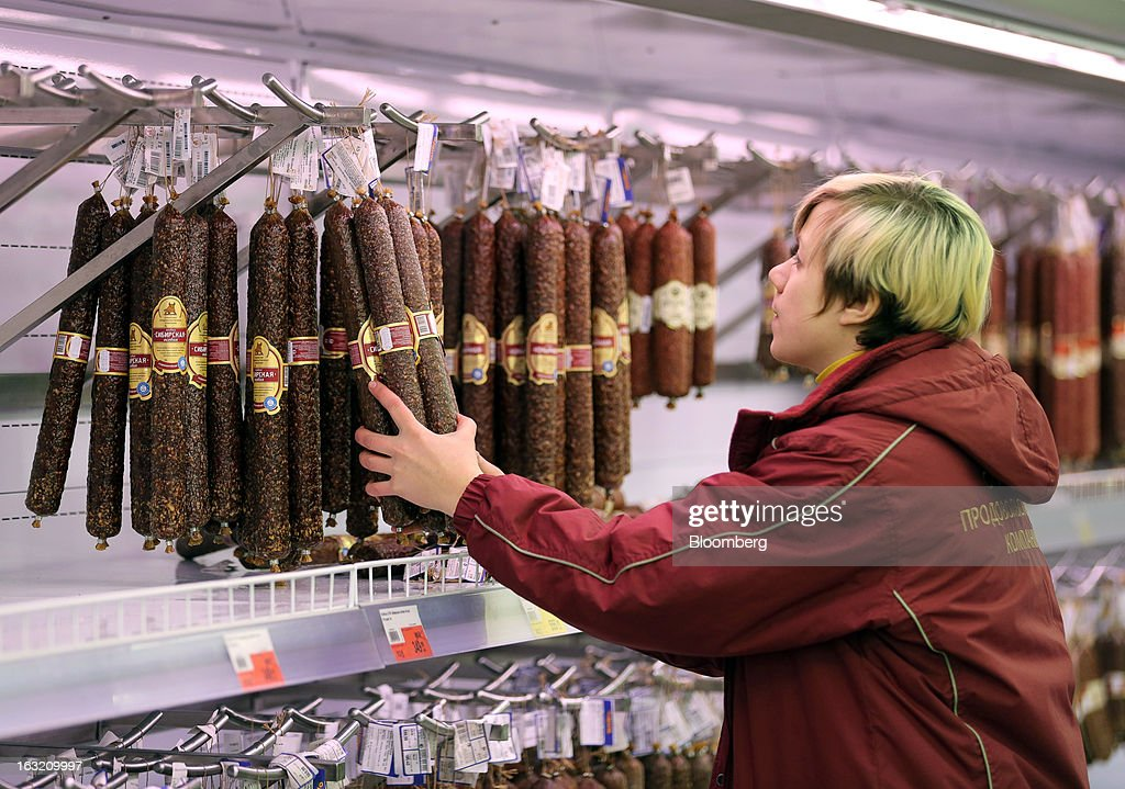 An employee arranges a display of preserved meat products in a cabinet inside a Lenta LLC supermarket in Prokopyevsk, Kemerevo region, Russia, on Wednesday, March 6, 2013. Lenta LLC, a Russian hypermarket operator controlled by TPG Capital, is selling its first bond to expand after using company funds for a leveraged buyout by the U.S. firm. Photographer: Andrey Rudakov/Bloomberg via Getty Images