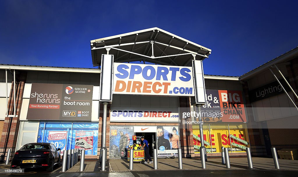 An employee arranges a display of sports balls outside a Sports Direct International Plc store ahead of opening in Urmston, U.K., on Saturday, Oct. 6, 2012. JJB Sports Plc, a U.K. sporting goods retailer, will close most of its stores with the remaining 20 being acquired by competitor Sports Direct International Plc, according to a statement from KPMG LLP, which was appointed as administrator to the Wigan, England-based company. Photographer: Paul Thomas/Bloomberg via Getty Images