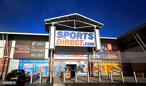 An employee arranges a display of sports balls outside a Sports Direct International Plc store ahead of opening in Urmston UK on Saturday Oct 6 2012...
