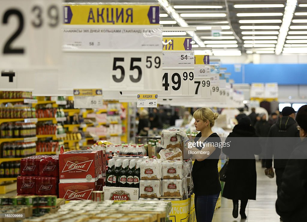 An employee arranges a display of Stella Artois and Bud beer in the aisle of a Lenta LLC supermarket in Prokopyevsk, Kemerevo region, Russia, on Wednesday, March 6, 2013. Lenta LLC, a Russian hypermarket operator controlled by TPG Capital, is selling its first bond to expand after using company funds for a leveraged buyout by the U.S. firm. Photographer: Andrey Rudakov/Bloomberg via Getty Images