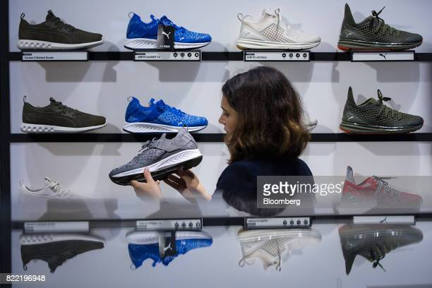 An employee arranges a men's running shoe display inside a Puma SE sportswear clothing store in Berlin Germany on Tuesday July 25 2017 Puma increased...