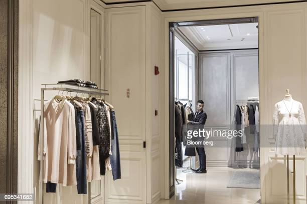 An employee arranges a piece of clothing on a mannequin inside a Christian Dior SE store in Shanghai China on Saturday June 10 2017 Christian Dior SE...