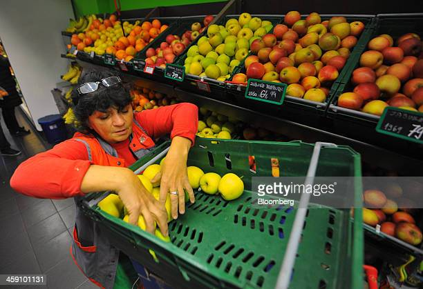 An employee arranges a tray of apples for display inside a Delhaize Group SA Maxi supermarket in Belgrade Serbia on Friday Dec 20 2013 Delhaize Group...
