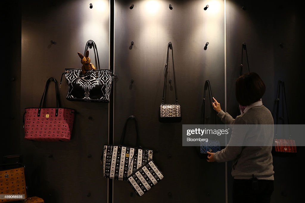 An employee arranges bags displayed for sale inside an MCM Holdings AG store on Garosugil street in the Gangnam district of Seoul, South Korea, on Sunday, Dec. 22, 2013. Consumer prices climbed 0.9 percent in November from a year earlier after a 0.7 percent increase in October that was the smallest gain since July 1999. Photographer: SeongJoon Cho/Bloomberg via Getty Images