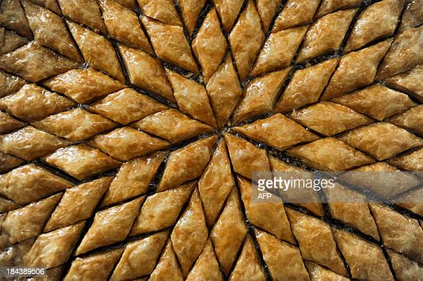 An employee arranges baklava pastries on October 13 2013 at a bakery in Pristina during the preparations for the Muslim feast of sacrifice known in...