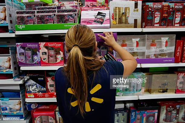 An employee arranges beauty product gift boxes displayed for sale at a WalMart Stores Inc location ahead of Black Friday in Los Angeles California US...
