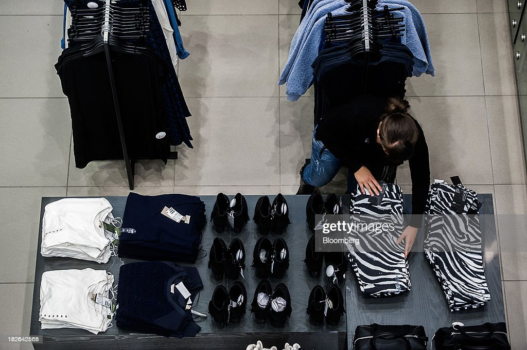 An employee arranges black and white clothes on display inside a Hennes & Mauritz AB (H&M) fashion store in Budapest, Hungary, on Wednesday, Oct. 2, 2013. 'The retail sales environment in Europe, especially in Spain, has become less challenging in the last few weeks, while the weather overall has also been more stable,' Anne Critchlow, a London-based analyst at Societe Generale, said. Photographer: Akos Stiller/Bloomberg via Getty Images