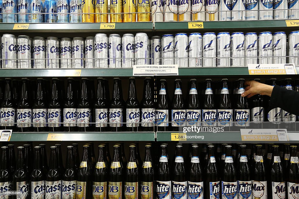 An employee arranges bottles of Hite Jinro Co. Hite beer at an E-Mart Co. store, a subsidiary of Shinsegae Co., in Incheon, South Korea, on Saturday, Dec. 21, 2013. Consumer prices climbed 0.9 percent in November from a year earlier after a 0.7 percent increase in October that was the smallest gain since July 1999. Photographer: SeongJoon Cho/Bloomberg via Getty Images