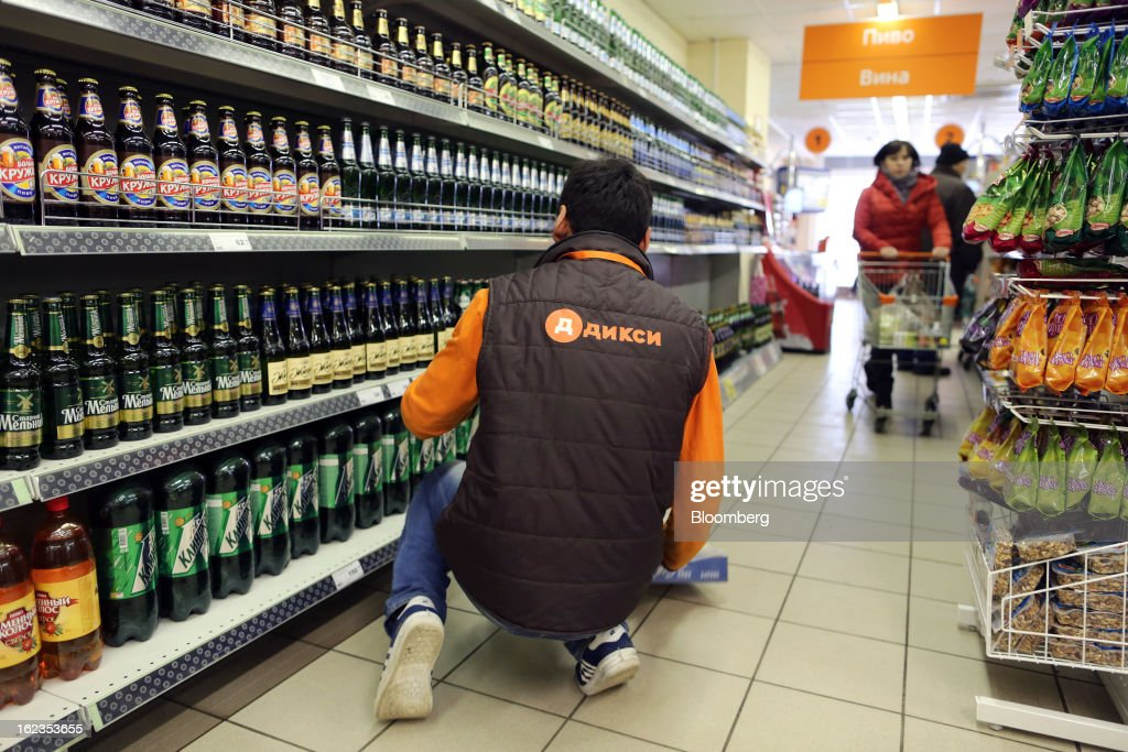 An employee arranges bottles of Russian beer in the alcohol section of a supermarket operated by OAO Dixy Group in Moscow, Russia, on Friday, Feb. 22, 2013. Russia's largest retailer by market value, OAO Magnit, is spending as much as $1.8 billion this year to compete against X5 Retail Group NV and OAO Dixy Group. Photographer: Andrey Rudakov/Bloomberg via Getty Images