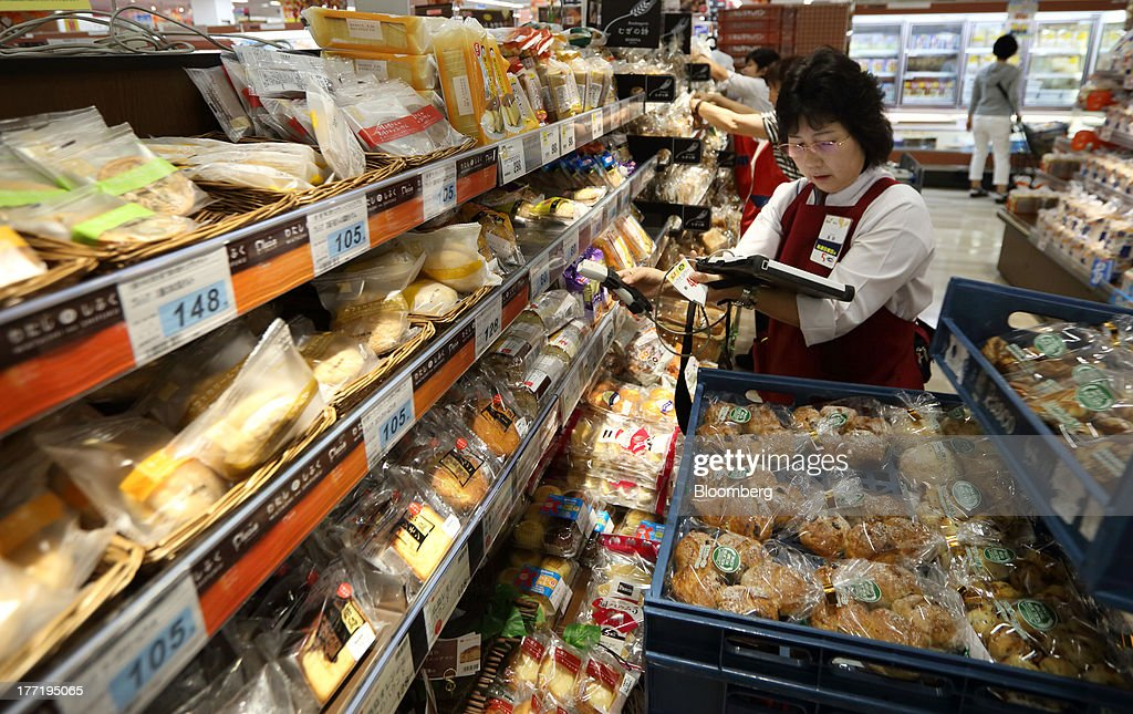 An employee arranges bread at a Daiei Inc. supermarket during a sale jointly held with Aeon Co. at a Daiei supermarket in Urayasu City, Chiba Prefecture, Japan, on Thursday, Aug. 22, 2013. Aeon's acquisition of 48.4 million Daiei shares will take place on Aug. 27 after the completion of tender offer yesterday, according to a statement to the Tokyo Stock Exchange released today. Photographer: Tomohiro Ohsumi/Bloomberg via Getty Images