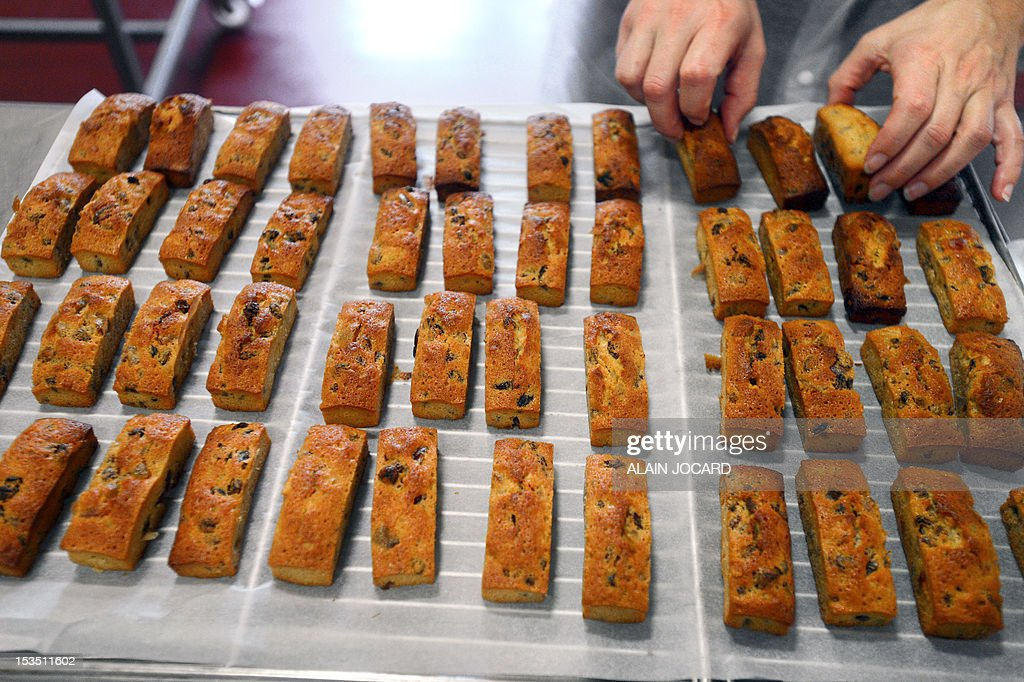 An employee arranges cakes on a railing on October 5, 2012 at a factory of French biscuits maker 'Saint-Michel' in Contres, western France.