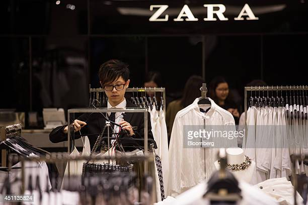 An employee arranges clothes at a Zara store operated by Inditex SA in Hong Kong China on Tuesday June 24 2014 Inditex which has increased profit...