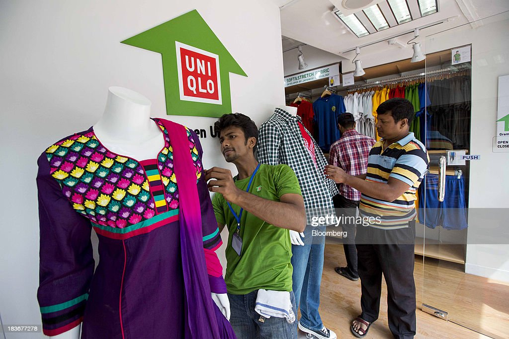 An employee arranges clothes on a mannequin display at the opening of a Grameen Uniqlo store, a joint venture between Fast Retailing Co. and Grameen Healthcare Trust, in the Paltan area of Dhaka, Bangladesh, on Saturday, Oct. 5, 2013. Fast Retailing, Asia's biggest clothing retailer, set up the venture with Grameen Healthcare Trust to design, make and sell clothes in Bangladesh. Photographer: Jeff Holt/Bloomberg via Getty Images