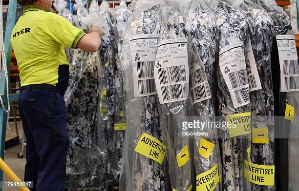 An employee arranges clothes onto sorting rails for scanning and dispatch at the Myer Holdings Ltd distribution center in Melbourne Australia on...