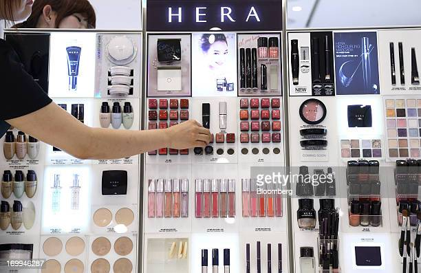 An employee arranges cosmetics at an Amorepacific Corp Hera cosmetics counter inside a Lotte Shopping Co Lotte Department Store inside the Lotte Mall...