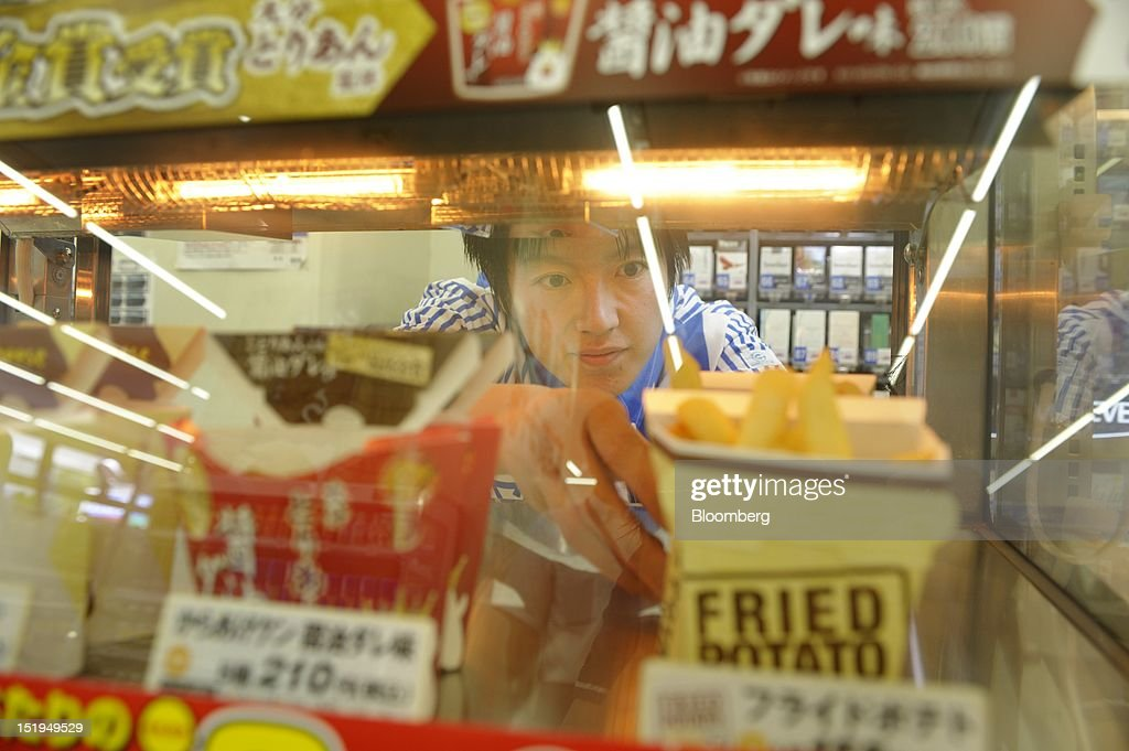 An employee arranges deep-fried foods on a shelf at a Lawson Inc. convenience store in Tokyo, Japan, on Friday, Aug. 31, 2012. Sales at Japan's convenience stores declined 3.3 percent in July from a year ago on a same-store basis, according to the Japan Franchise Association. Photographer: Akio Kon/Bloomberg via Getty Images